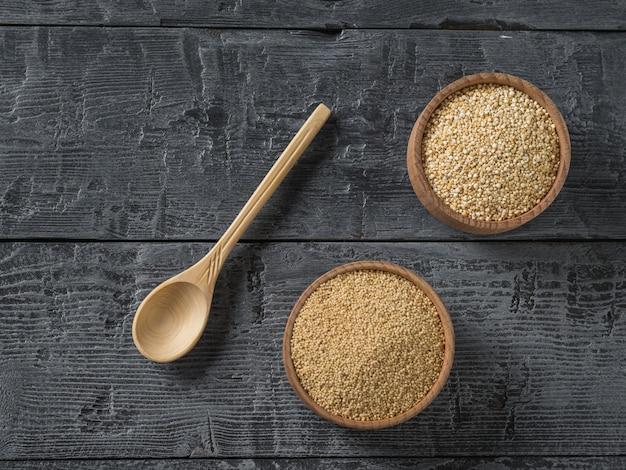 Duas bacias de madeira com sementes de amaranto e quinoa e colher de pau em uma mesa de madeira escura. comida sem glúten.