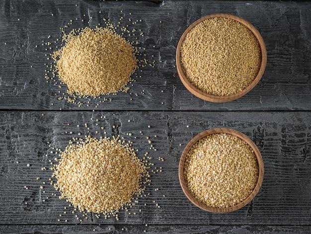 Duas bacias de madeira com sementes de amaranto e quinoa em uma mesa de madeira escura. comida sem glúten.