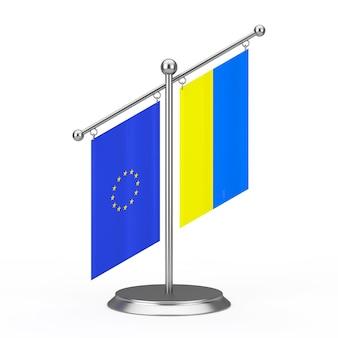 Duas bandeiras de tela de mesa da ucrânia e da união europeia no pedestal de pináculo de aço em um fundo branco. renderização 3d