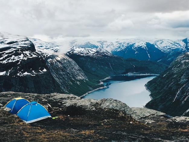 Duas barracas azuis estão de pé diante de uma maravilhosa vista para a montanha