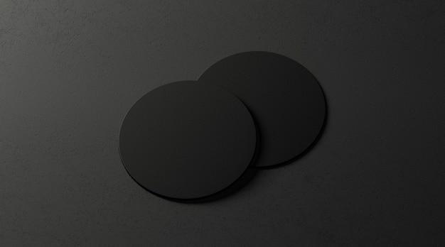 Duas bases para copos de cerveja pretas em branco na superfície escura