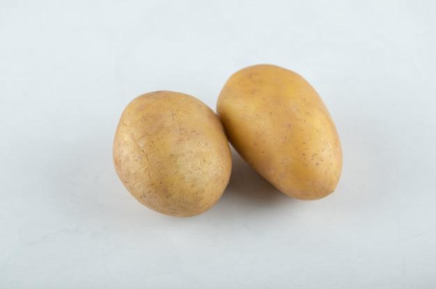 Duas batatas frescas em fundo branco.