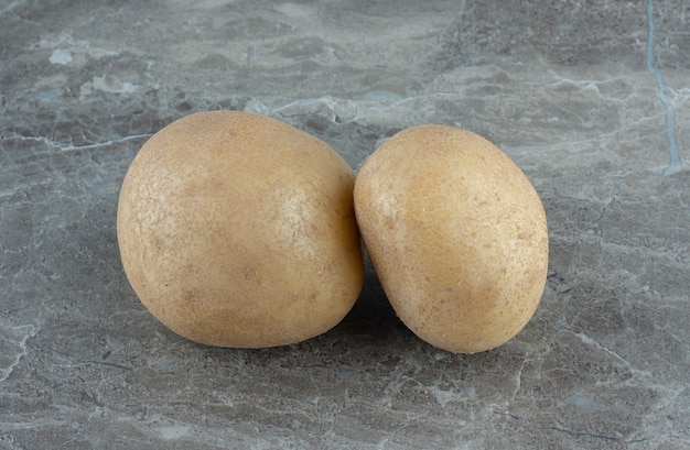 Duas batatas maduras, na mesa de mármore.