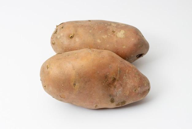 Duas batatas orgânicas isoladas em branco