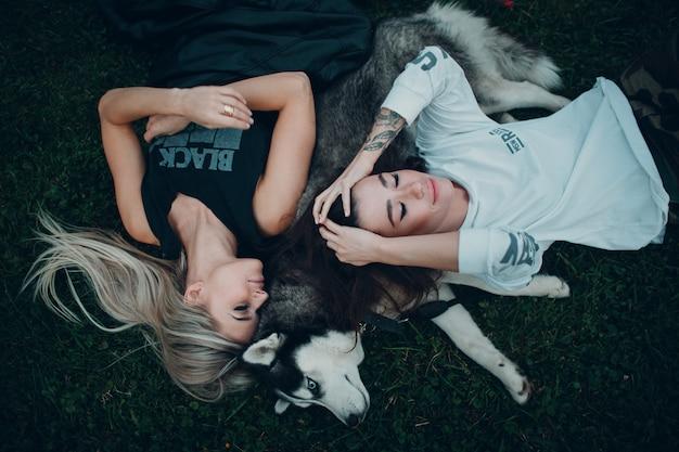 Duas bela jovem deitado com cachorro husky na grama