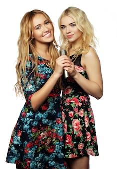 Duas belas garotas com um microfone cantando e se divertindo