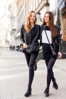 Duas belas garotas posando juntas ao ar livre. humor urbano do estilo de vida. fundo da cidade do centro. melhores amigas vestindo roupa preta casual de outono.