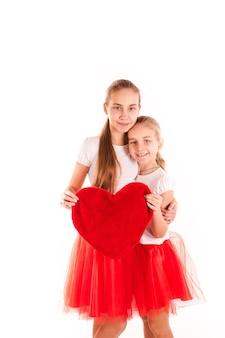 Duas belas garotas segurando coração vermelho isolado. conceito de amor e felicidade de são namorados.