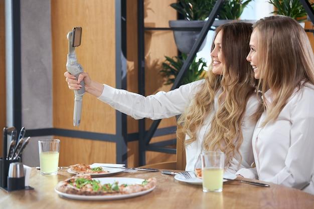 Duas belas jovens blogueiras sorrindo fazendo selfie