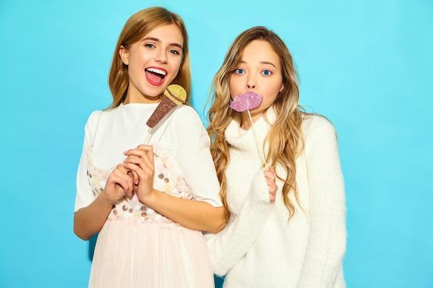 Duas belas jovens cantando com microfone falso de adereços. na moda mulheres com roupas de verão casual. modelos engraçados isolados na parede azul