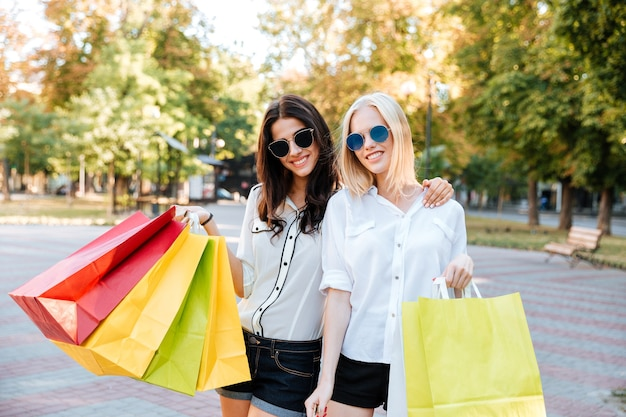 Duas belas jovens fazendo compras na cidade e olhando para a frente