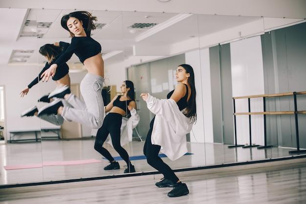 Duas belas meninas delgadas fazendo dança e ginástica no salão de dança