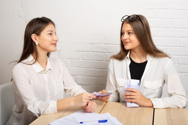 Duas belas moças à mesa no escritório com dinheiro do euro