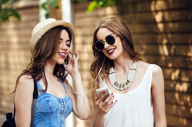 Duas belas moças caminham pela cidade e ouvem música