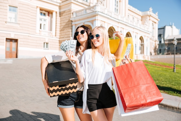 Duas belas moças caminhando na rua carregando sacolas de compras