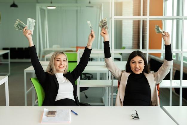 Duas belas moças no escritório à mesa com dólares