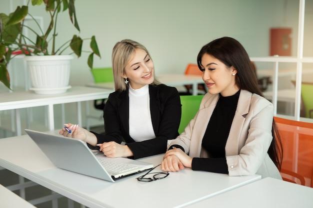 Duas belas moças no escritório à mesa com um laptop