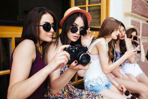 Duas belas moças segurando uma câmera vintage
