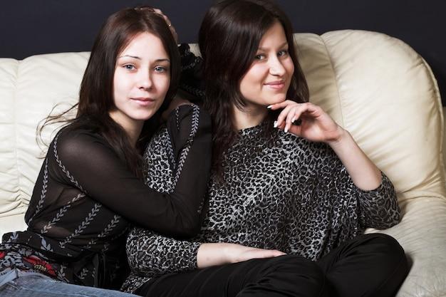 Duas belas modelos, vestidas com sitteng desgaste ocasional no sofá