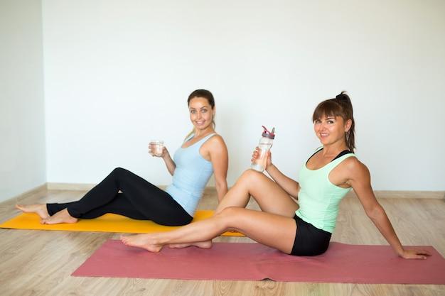 Duas belas mulheres adultas praticam esportes em casa