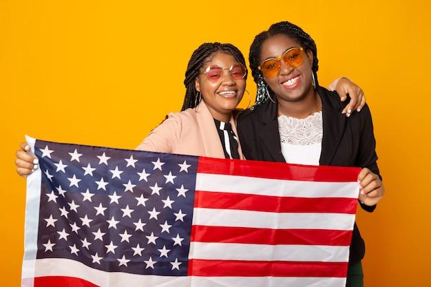 Duas belas mulheres africanas com a bandeira americana em fundo amarelo