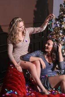 Duas belas mulheres comemorando o natal junto com o vestido da moda. natal em casa