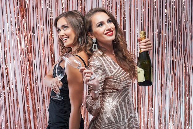 Duas belas mulheres elegantes, bebendo champanhe contra decoração brilhante