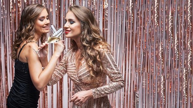 Duas belas mulheres elegantes em vestidos de noite, bebendo champanhe.