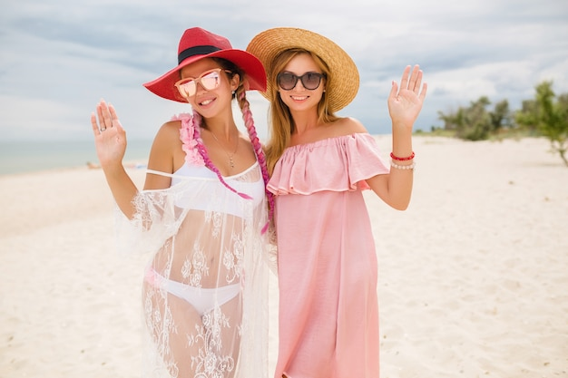Duas belas mulheres elegantes na praia de férias, estilo de verão,