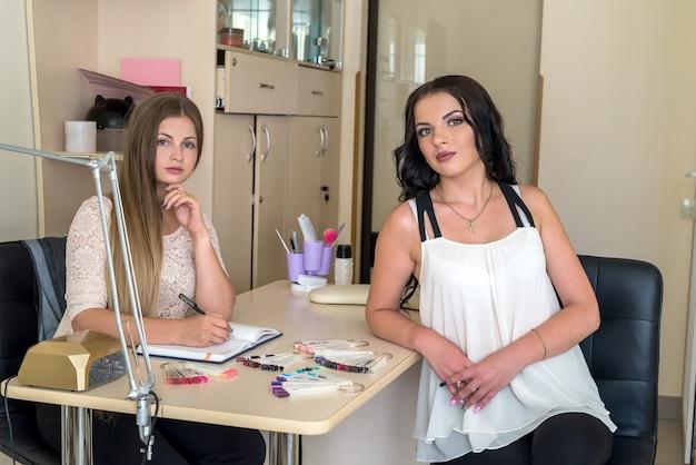 Duas belas mulheres em salão de beleza com paleta de unhas