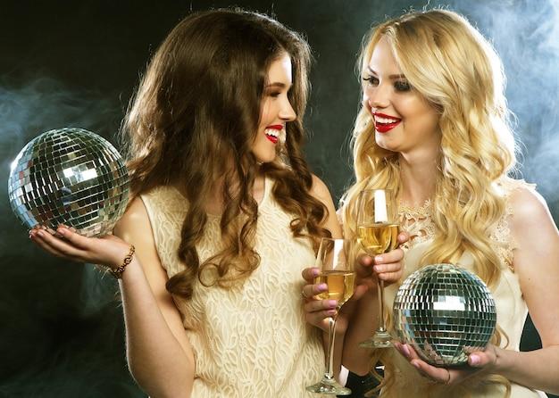 Duas belas mulheres jovens com taças de vinho e bola de discoteca.