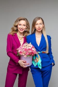 Duas belas mulheres loiras brancas com maquiagem vestindo elegantes ternos magenta e azuis com jaquetas e calças, sorrindo para a câmera. menina à esquerda segurando lindas flores na caixa de chapéu.