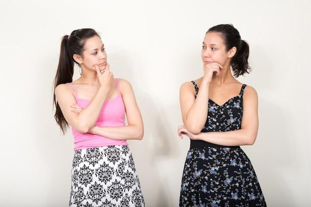 Duas belas mulheres multiétnicas como irmãs juntas em branco