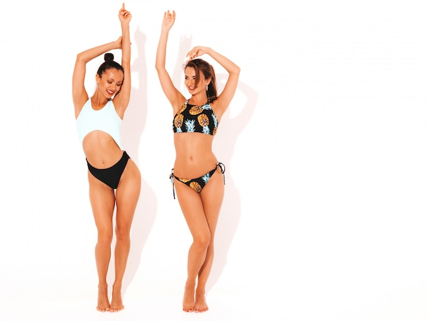 Duas belas mulheres sorridentes sexy em lingerie de natação. modelos quentes na moda se divertindo. meninas isoladas. levantando as mãos, comprimento total