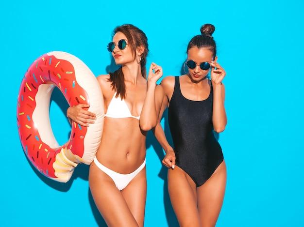 Duas belas mulheres sorridentes sexy em trajes de banho branco e preto de verão. garotas de óculos de sol. modelos positivos se divertindo com colchão inflável donut lilo. isolado na parede azul