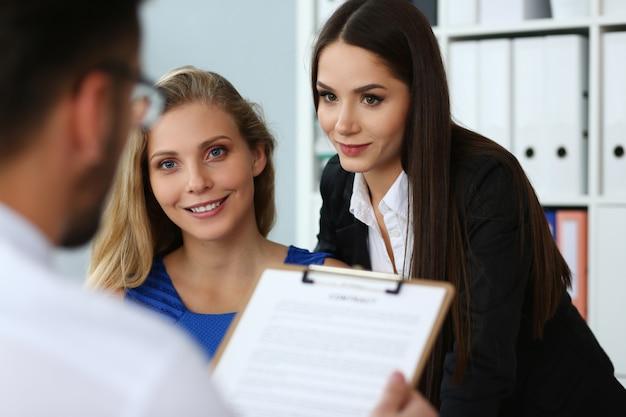 Duas belas mulheres trabalhando com colega no escritório