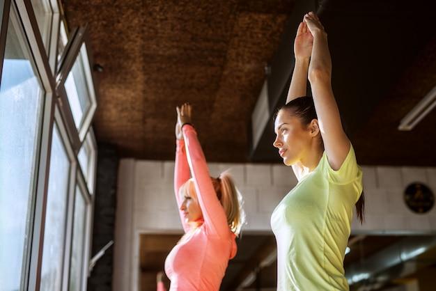 Duas belas senhoras em pé em uma academia, esticando os braços após o treino