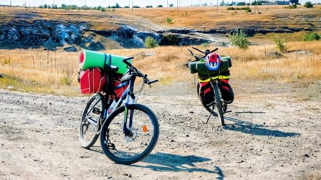 Duas bicicletas estacionadas com coisas de viajante em uma estrada rural, ravina e campos na moldávia