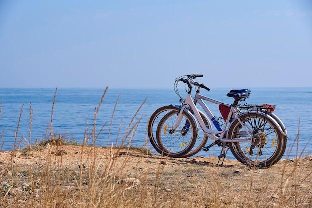 Duas bicicletas na praia no fundo um mar azul.