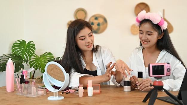 Duas blogueiras adolescentes apresentando produtos de beleza e vídeos ao vivo nas redes sociais.