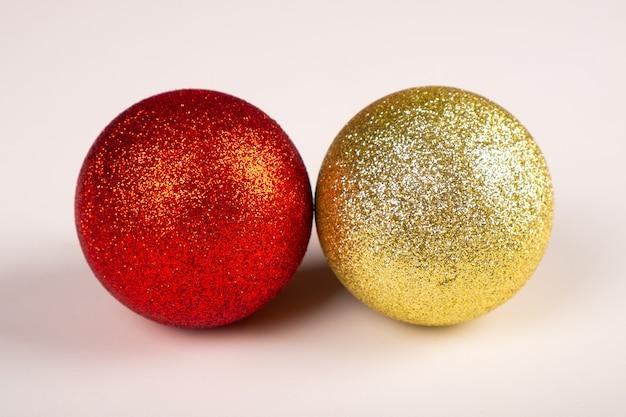 Duas bolas brilhantes de natal, amarelas e vermelhas.