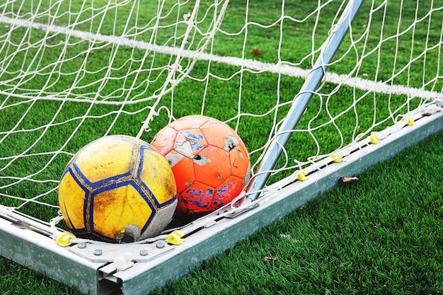 Duas bolas de futebol gasto no canto do gol no campo de futebol verde