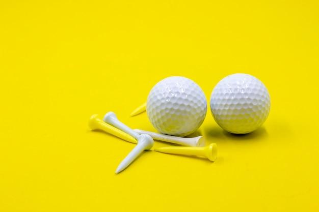Duas bolas de golfe estão em fundo amarelo com tees