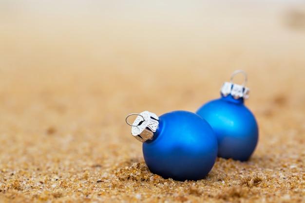 Duas bolas de natal azuis na costa arenosa do oceano