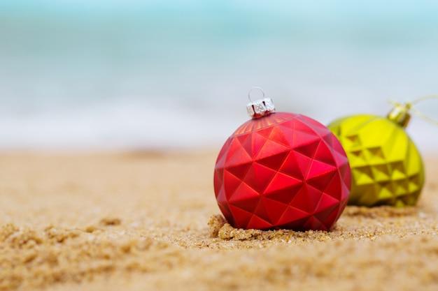 Duas bolas de natal na costa arenosa do oceano