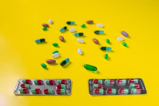 Duas bolhas com as cápsulas coloridas que encontram-se entre os comprimidos em um amarelo. estilo de vida saudável.