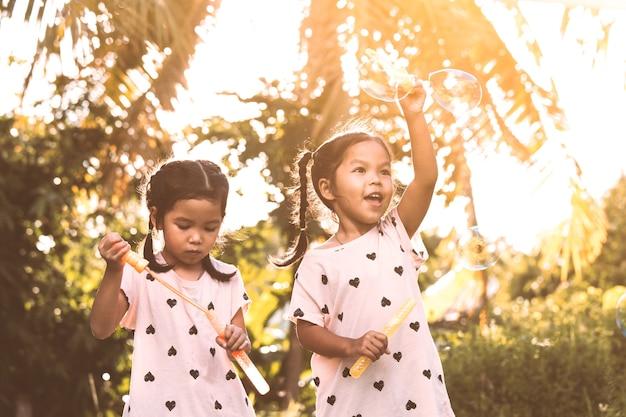 Duas bonitas crianças asiáticas que se divertem para jogar com bolhas juntas ao ar livre ao pôr do sol