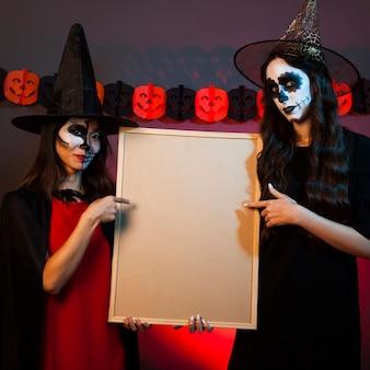 Duas bruxas segurando quadro branco