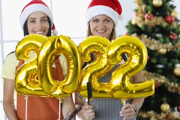 Duas cabeleireiras sorridentes, uniformizadas, seguram os números 2022 e uma tesoura com pente