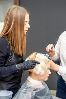Duas cabeleireiras tingindo o cabelo de uma jovem mulher caucasiana em um salão de cabeleireiro